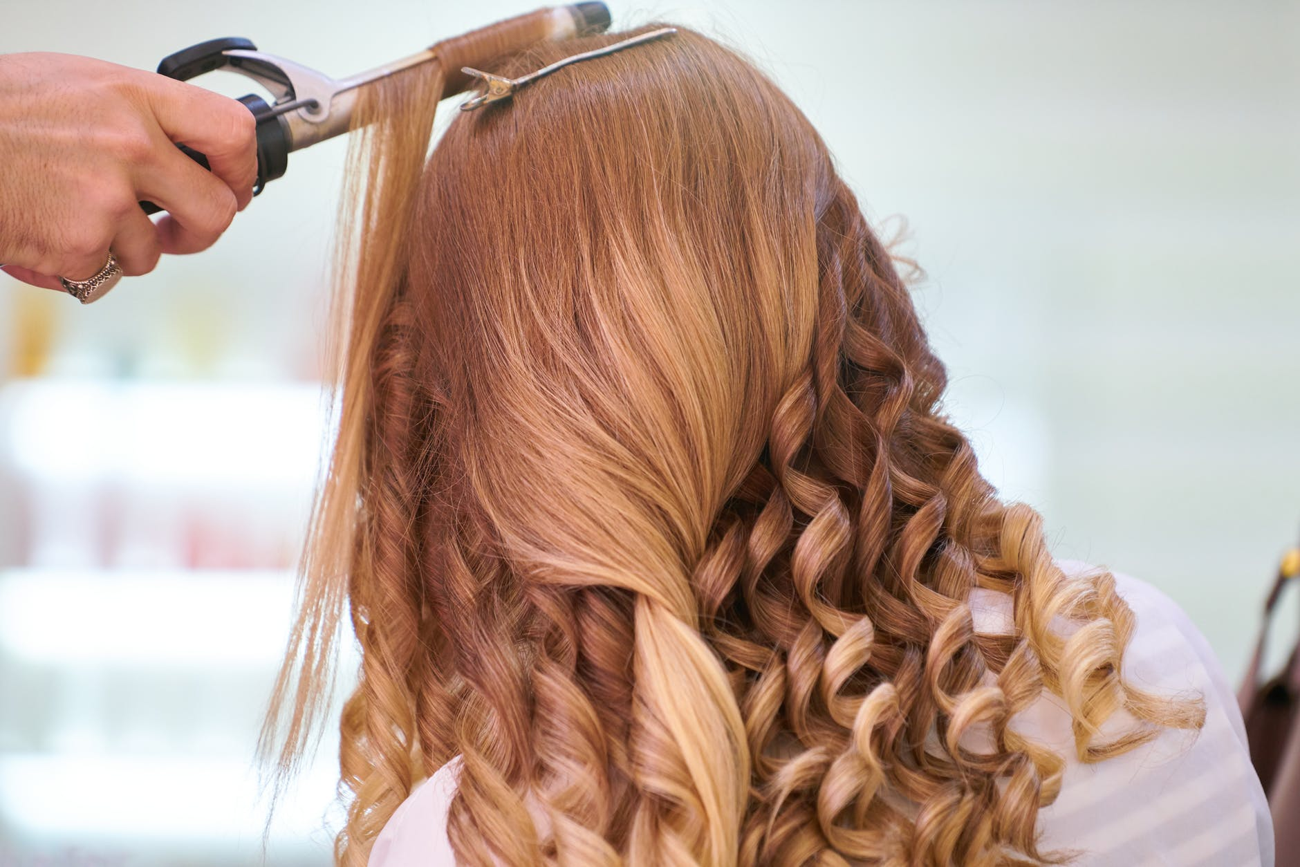 A woman getting her hair curled